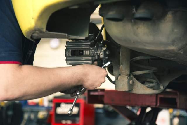 Imagem de um mecânico consertando um carro com bateria em curto