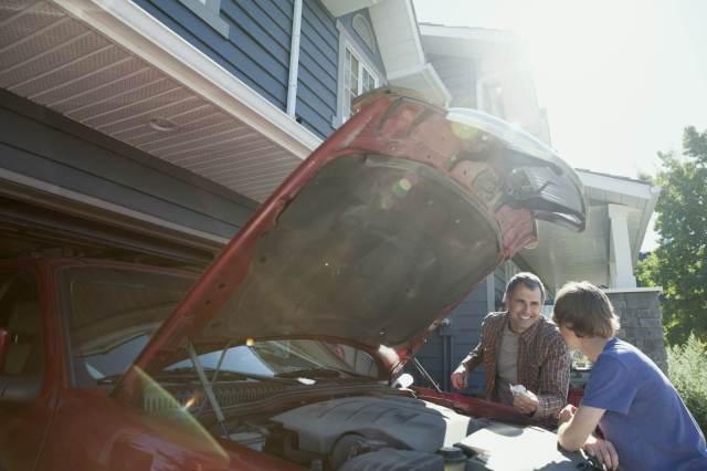 pai e filho conversando em frente ao carro com capô aberto
