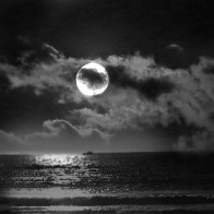 Black & White photo of beach merge with moon behind clouds.