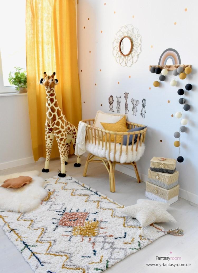 Gemütliches Babyzimmer mit Holztönen und Senfgelb, mit Rattanwiege, kuscheligem Teppich und passender Deko