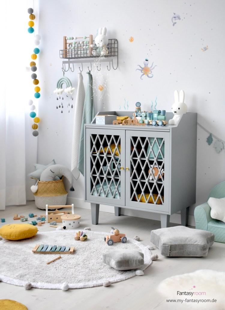 Kinderzimmer mit grauer Kommode und Holzspielzeug
