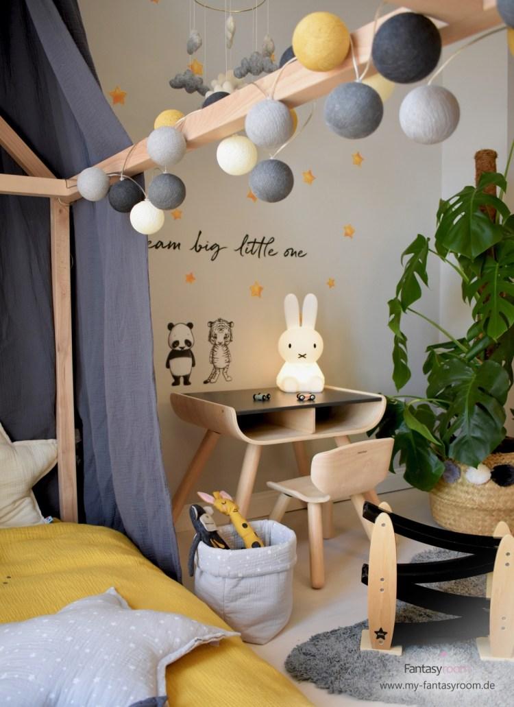 Lichterkette am Hausbett im stylischen Kinderzimmer in Senfgelb und Grau