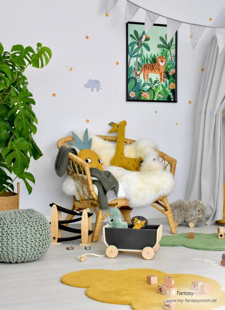 Gemütlicher Sitzplatz im Dschungelzimmer mit Korbsessel, Lammfellen und Kuschelkissen