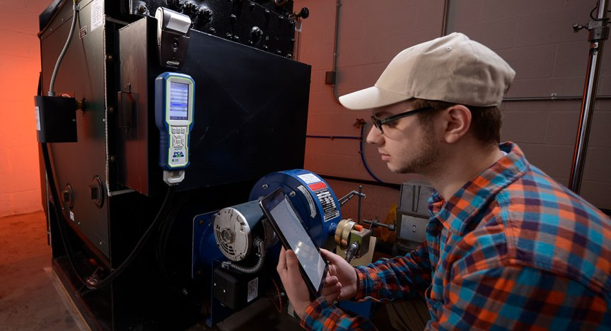 Technician checking measurements on tablet while tuning commercial boiler with PCA 400 Combustion & Emissions Analyzer.