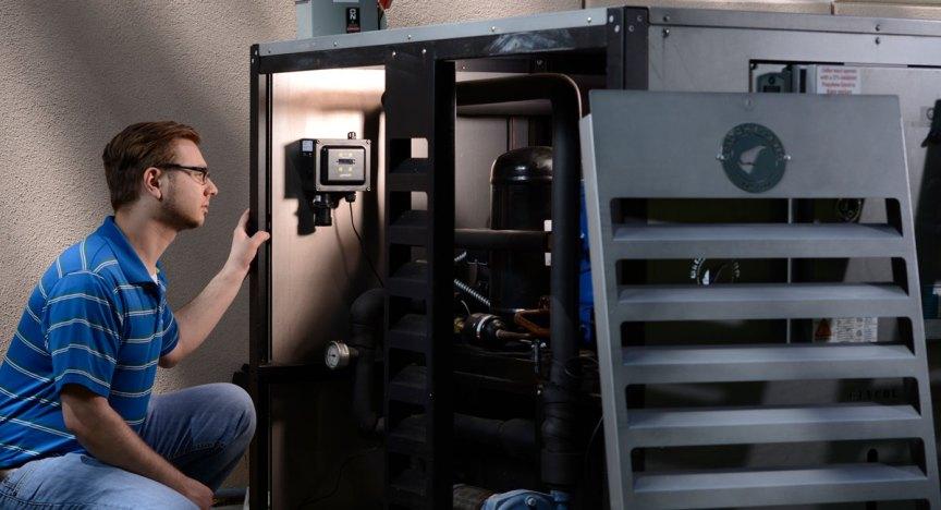 HVAC technician inspecting gas monitor near chiller.