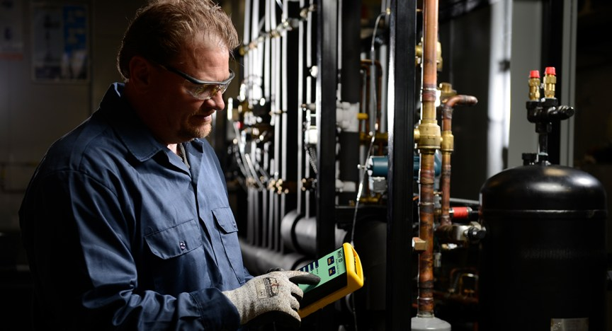 Technician testing refrigerant purity using the Neutronics Mini ID.