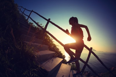 Woman jogging at sunrise up stairs