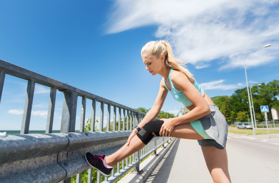 Female athlete adjusting knee brace during a walk or run