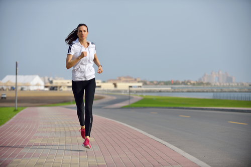 Woman running next to a road with city in background
