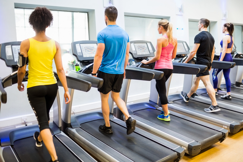 Group of people walking for fitness on treadmills