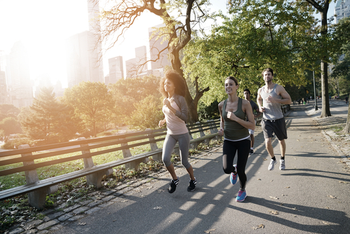 3 people jogging on an urban park path