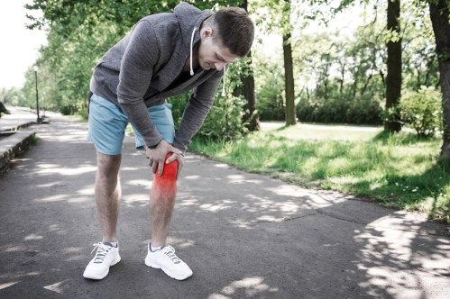 Man holding sore knee after jogging
