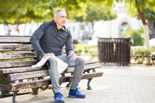 Male walker taking a rest on park bench
