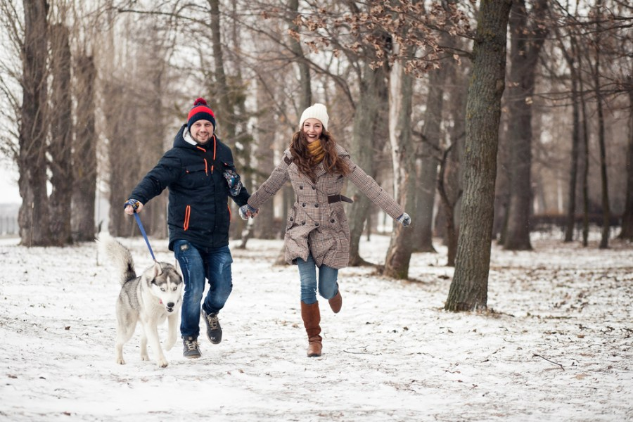 Couple having fun walking dog in winter snow