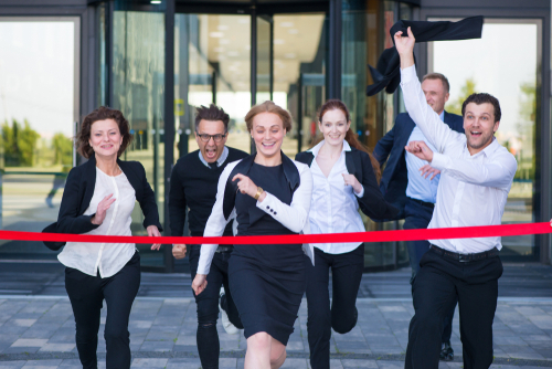 Office workers running and reaching the finish line