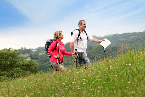 Couple hiking a hill with poles