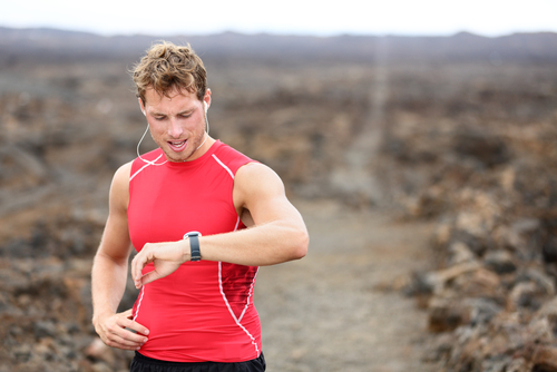 Man checking fitness watch after long jog