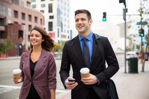 Happy male and female businesspeople walking