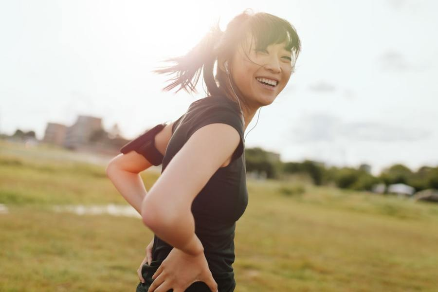 Sporty woman smiling in the sunshine outside