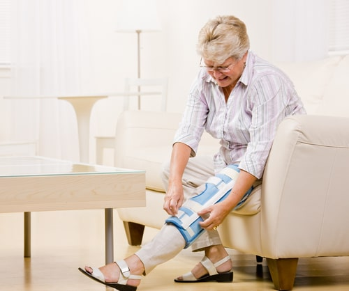Older woman adjusting knee brace