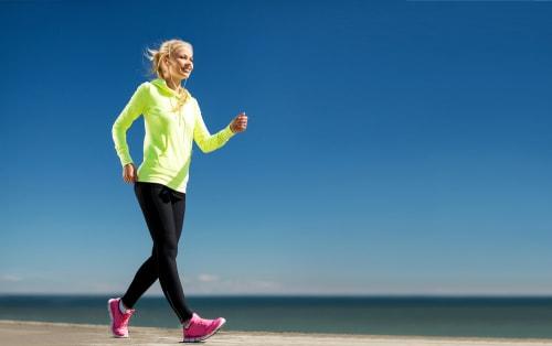 Woman power walking for fitness near the ocean