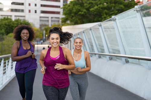 3 women power walking on a city bridge
