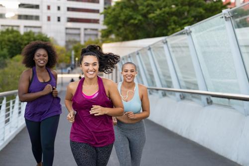 3 women power walking on a city bridge