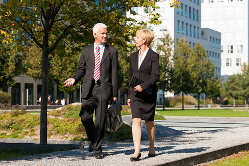 Older business people walking in a park