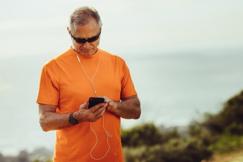 Athletic senior man checking phone during exercise