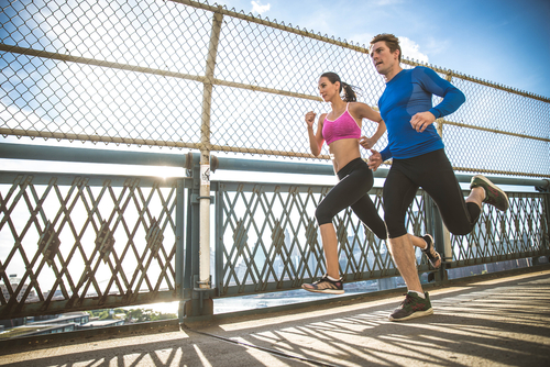 Couple jogging over a bridge in a city