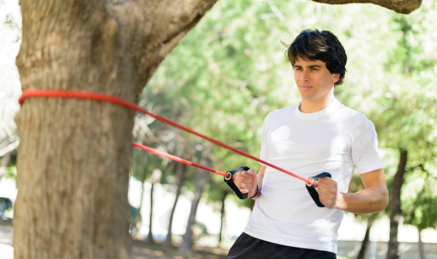 Man exercising with a resistance band in the park
