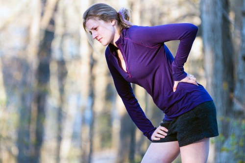 Female jogger holding her back - lower back pain concept