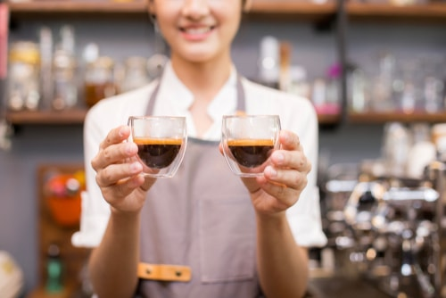 Barista holding shots of espresso
