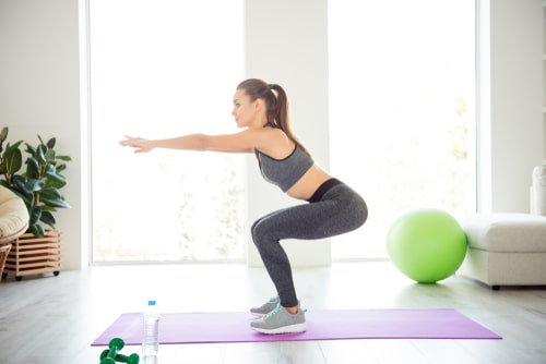 Woman doing bodyweight squats at home