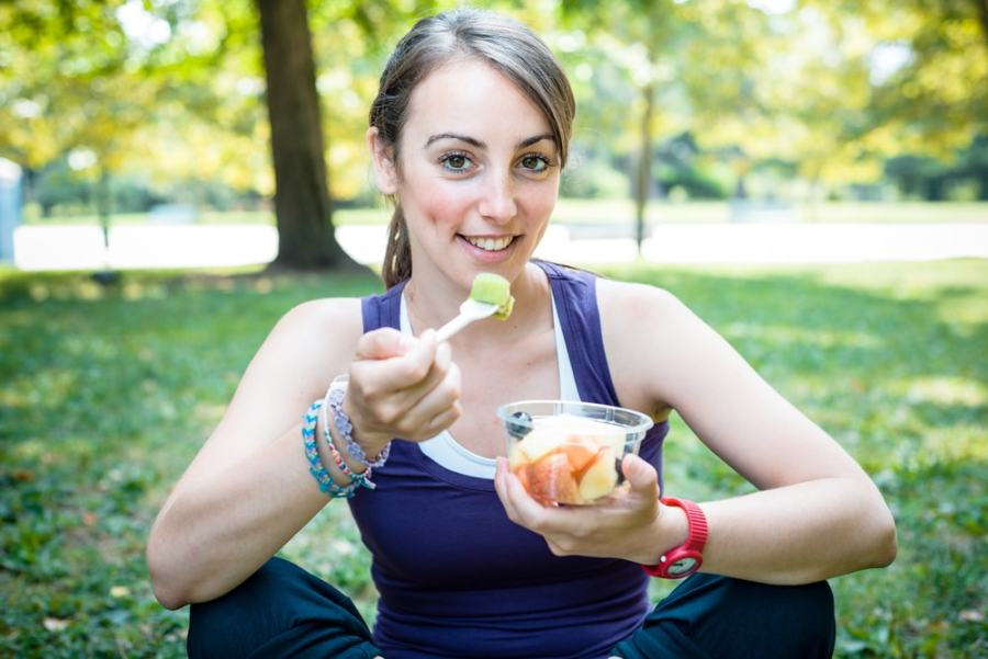 Sporty woman eating healthy fruit in the park