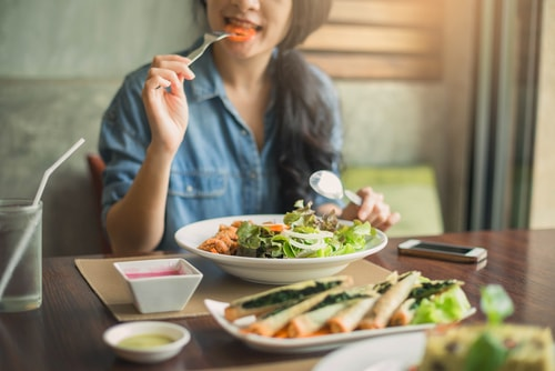 Woman eating a healthy salad and meal
