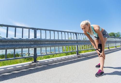 Female fitness walker holding sore knee