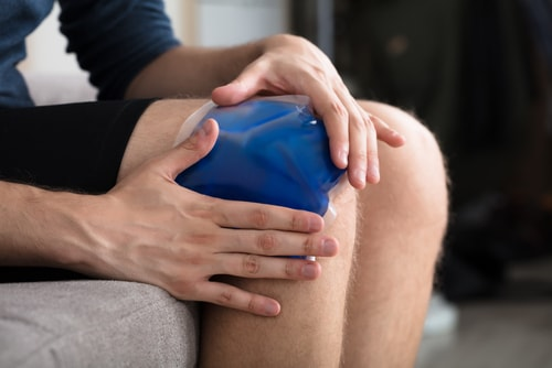 Man holding ice pack on outside of knee