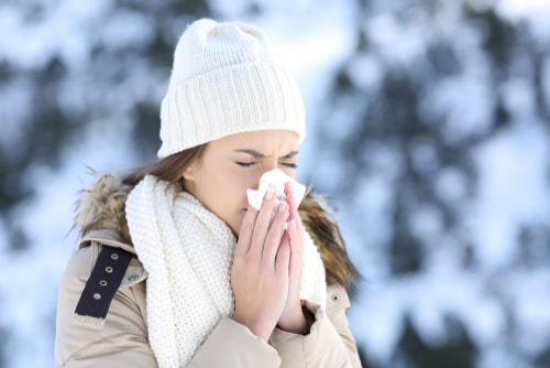Woman sneezing from a cold in winter