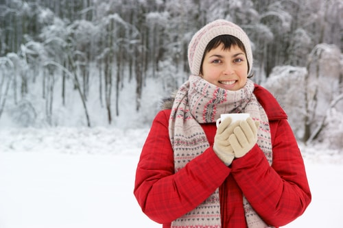 Woman bundled up in snowy park in winter