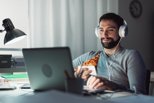 Man staying up late eating junk food and watching internet