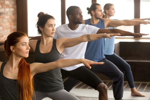Men and women doing yoga class together