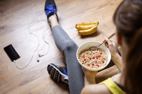 Woman eating a healthy oatmeal breakfast before a walk