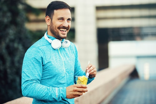 Sporty man eating healthy fruit during a walk