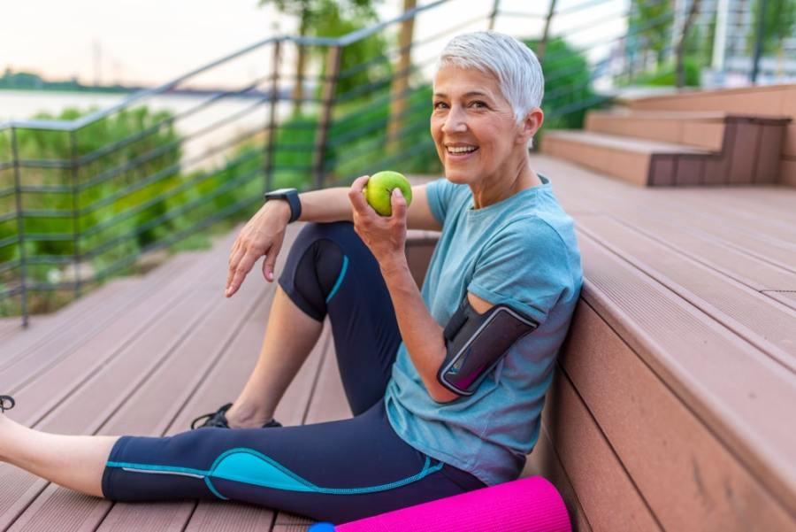 Sporty woman taking a break eating an apple