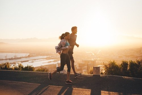 Man and woman fitness walking above a city