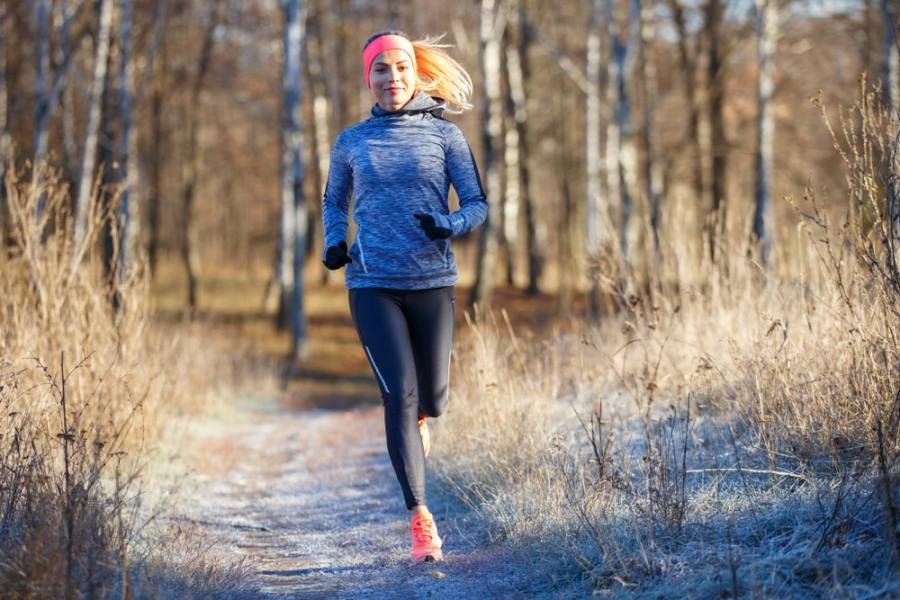 Woman running for fitness in a winter park