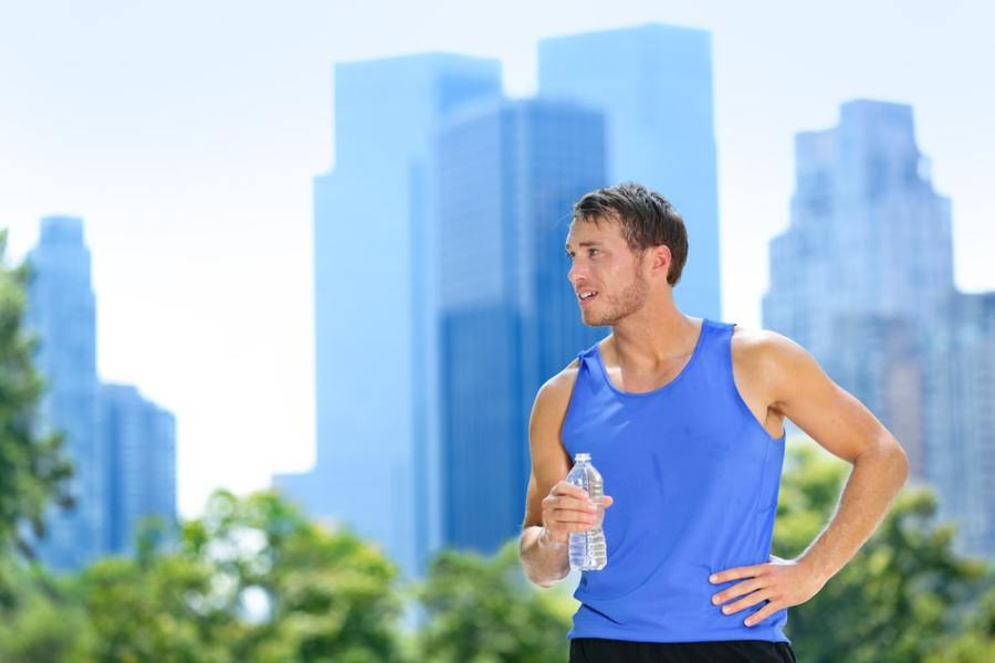 Man drinking water bottle during hot summer exercise