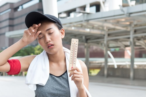Female walker holding thermometer - hot weather concept