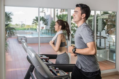 Man and woman running on treadmill at hotel